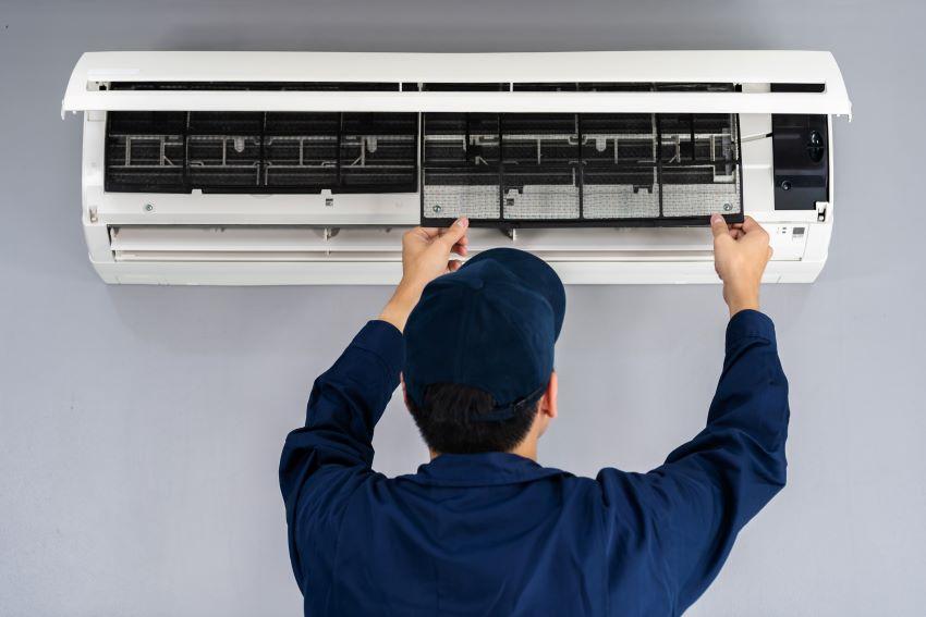 Técnico haciendo tareas de mantenimiento del aire acondicionado.